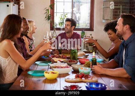 Sechs junge Erwachsene Freunde sitzen am Tisch für eine Dinner-party - Stockfoto