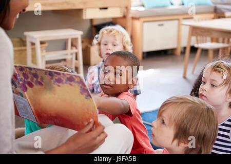 Schülerinnen und Schüler in der Montessori Schule betrachten Buch mit Lehrer
