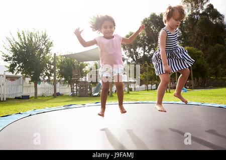 Kinder in der Montessori Schule Spaß am Outdoor-Trampolin - Stockfoto