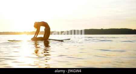 Frau auf einem SUP Yoga machen - Stockfoto