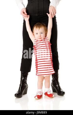 Mutter Holding Tochter übergibt erste Schritte isoliert auf weiss - Stockfoto
