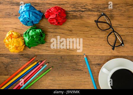 mit Hilfe eines Bleistifts hellblaue Farbe, Zeichnung auf dem Exemplar des Hintergrunds Holzboden mit Papierkugeln - Stockfoto