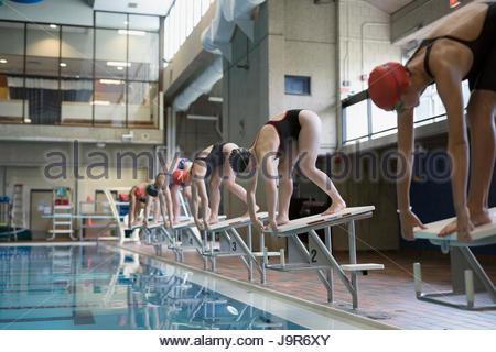 Junge Frauen Schwimmer bereit, stehend auf der Startplattform am pool - Stockfoto