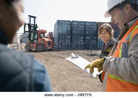 Arbeitnehmer mit Zwischenablage sprechen in Industriebehälter Hof - Stockfoto