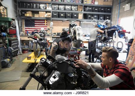 Motorradmechanik sprechen, Befestigung Motorrad in Autowerkstatt - Stockfoto