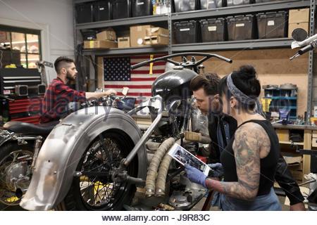 Motorradmechanik mit digital-Tablette Befestigung Motorrad in Autowerkstatt - Stockfoto