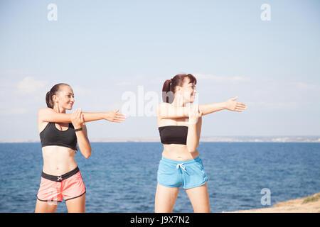 zwei Girls spielen Sport Fitness am Strand - Stockfoto