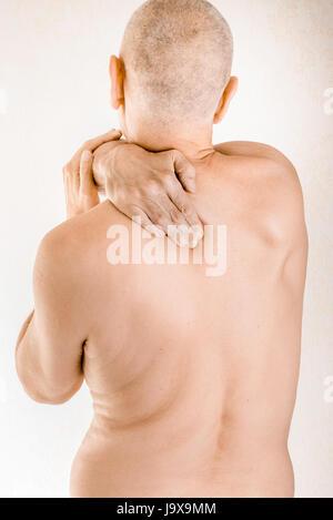 Mann massiert seine oberen Rücken, den Trapezius Muskel, wegen einem ...