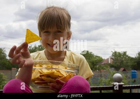 Kleines Mädchen mit Chips in ihrer hand - Stockfoto