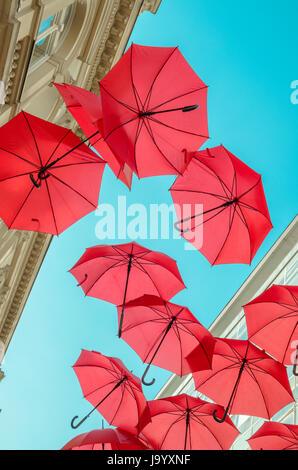 Viele rote Schirme fliegen in den Himmel. - Stockfoto