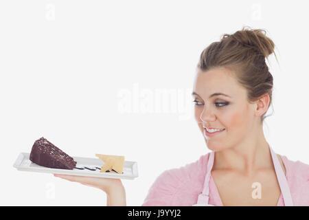 Nahaufnahme der jungen Frau betrachten Gebäck vor weißem Hintergrund - Stockfoto