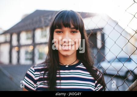 Porträt von schönen weiblichen Modell stehen im freien hautnah. Hispanic Frau Blick in die Kamera und lächelnd. - Stockfoto