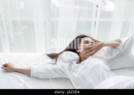 Asiatische Frau schöne junge lächelnde Frau sitzt auf dem Bett und stretching am Morgen im Schlafzimmer nach dem - Stockfoto