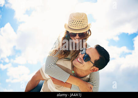 Hübscher junger Mann mit seiner liebevollen Frau oder Freundin Spaß am Sommer Urlaub Huckepack Reiten gegen einen - Stockfoto