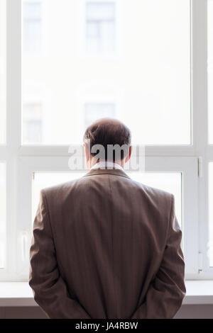 Porträt eines Mannes im Anzug am Fenster. Snapshot von der Rückseite - Stockfoto