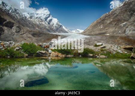 Blauer See: im Spiegel des Wassers reflektiert, hellen Himmel mit weißen Wolken, grüne Pflanzen am Rand des Wassers - Stockfoto
