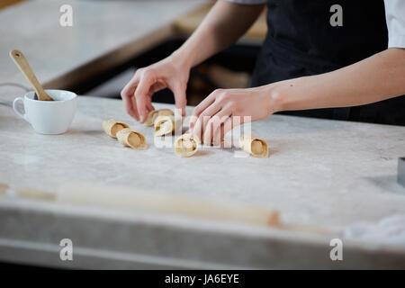 Horizontale drinnen Ernte Schuss von Händen Frau arbeiten mit kneten und Nudeln in Küche bilden. - Stockfoto