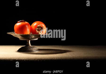 Vintage Messing Schale mit Kaki Früchten auf Leinwand Oberfläche - Stockfoto