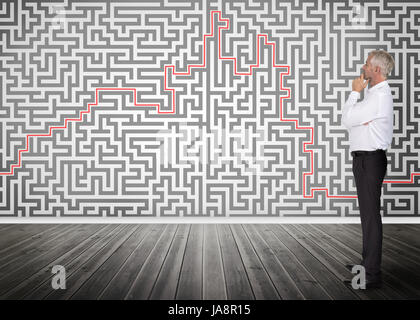 Nachdenklich Geschäftsmann stehen und blickte in ein Labyrinth an einer Wand - Stockfoto