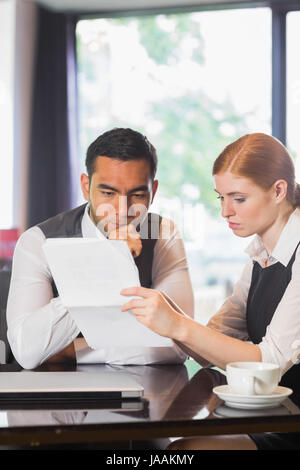 Ernsthafte Business Partner arbeiten zusammen in einem Café an Dokumenten - Stockfoto
