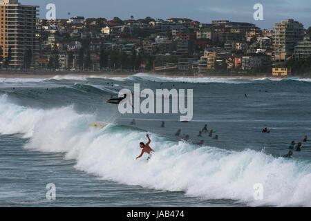 Dramatische Szene mit Surfer fliegen hoch in der Luft am Manly Beach, Sydney, New South Wales, Australien - Stockfoto