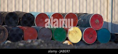 Bunte 50 Gallonen Metallfässer gesehen am Ende mit einer Reihe gestapelt andererseits gegen ein Gebäude aus Metall. - Stockfoto