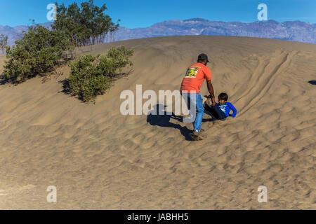 Menschen, Touristen, Vater und Sohn, spielen, Rutschen auf Sand, Mesquite flache Sanddünen, Death Valley Nationalpark, - Stockfoto