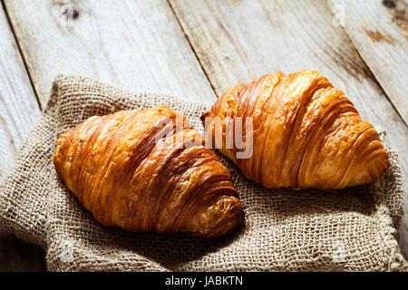 Zwei frische Croissants auf Sackleinen Textil auf rustikalen Holztisch. Detailansicht - Stockfoto