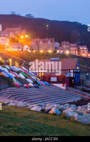 Sehr malerische Dorf an der Küste (Abend-Ansicht) Leuchten in Häusern am Meer & bunte Boote sind auf Helling - Runswick - Stockfoto