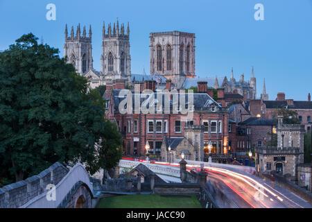 Stadtmauer, Straße über Lendal Bridge & 3 dunklen Abendhimmel, ikonischen Türme des Münsters gegenübergestellt Leuchten von Straßenlaternen & Lichtspuren - York, GB, UK.