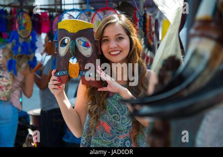 Nahaufnahme einer jungen lächelnden schönen Frau in ihren Händen hält eine Maske aus Holz, in einem Shop-Hintergrund - Stockfoto