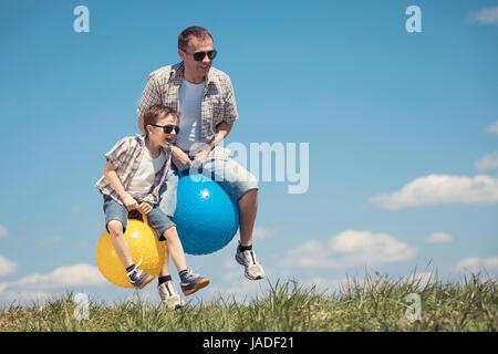 Vater und Sohn spielen auf dem Feld in der Tageszeit. Leute, die Spaß im Freien. Sie springen auf aufblasbaren Bällen - Stockfoto