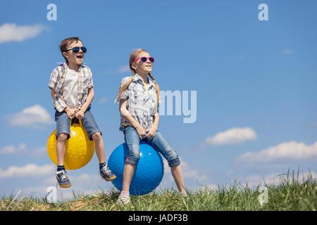 Bruder und Schwester spielen auf dem Feld in der Tageszeit. Kinder haben Spaß im Freien. Sie springen auf aufblasbaren - Stockfoto