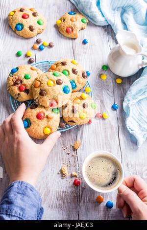 Hausgemachte Kekse mit bunten Pralinen mit Tasse Kaffee auf alten weißen Holztisch. - Stockfoto