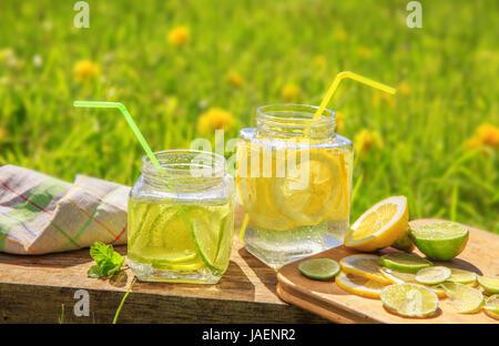 Zitronen und Limetten Scheiben in Gläsern im Sommer Holz Hintergrund. - Stockfoto