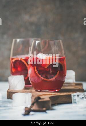 Blutorange und Erdbeere Sommer Sangria. Frucht, erfrischende rose Wein Cocktails in Gläser mit Eis, dunklen Hintergrund, - Stockfoto