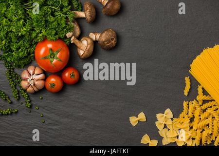 Italienisches Essen Konzept. Pasta Zutaten. Cherry-Tomaten, Spaghetti Pasta, Rosmarin und Gewürze - Stockfoto