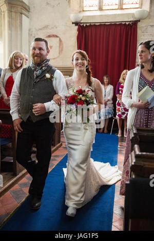 Lächeln, Braut und Bräutigam zu Fuß durch die Insel in einer Kirche. - Stockfoto