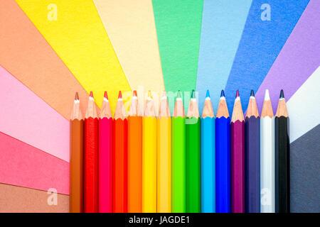 Nahaufnahme Makroaufnahme scharf bunte Bleistifte aufgereiht in einer Reihe auf bunte Blätter - Stockfoto