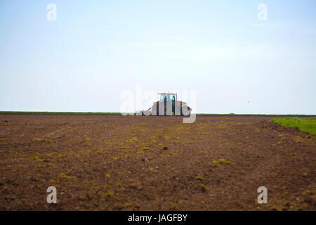 gelbe Traktor Pflügen Nutzpflanzen in Feld auf klare blaue heißen Sonnentag - Stockfoto