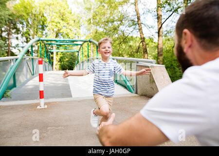 Kleiner Junge läuft in die Arme des Vaters, sonnigen Sommertag. - Stockfoto