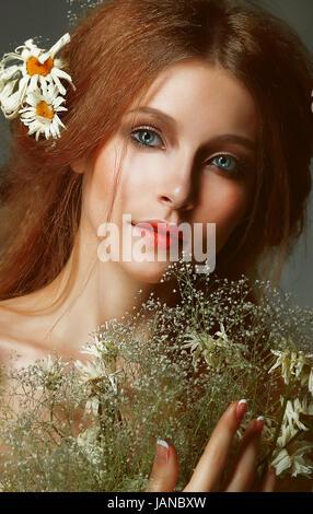 Pure Schönheit. Auburn Girl holding Bouquet von Wiesenblumen. Zärtlichkeit - Stockfoto