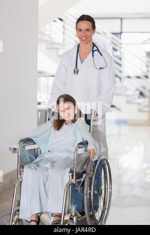 Arzt mit einer Frau in einem Rollstuhl in einem Krankenhaus - Stockfoto