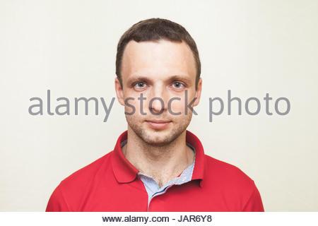 Nahaufnahme Studioportrait von jungen Erwachsenen europäischen Mann im roten Polo-shirt - Stockfoto