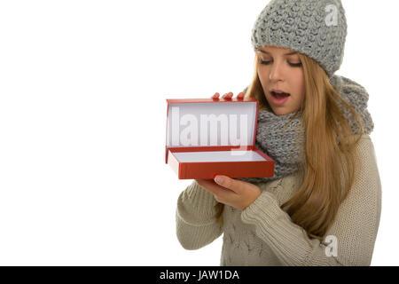 Junge Frau / Mädchen Trägt Strickware Und Schaut heute in Eine Geschenkverpackung. Wie Eine Überraschung Zu Fernsehsendern - Stockfoto