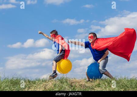Vater und Sohn spielen Superhelden in der Tageszeit. Leute, die Spaß im Freien. Sie springen auf aufblasbaren Bällen - Stockfoto