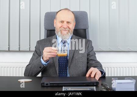 Bild von einem nachdenklichen Manager in einer Kaffeepause im Büro - Stockfoto