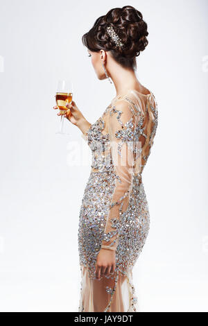 Elegante Dame in Silber-goldenes Kleid mit Weinglas von Champagne. Luxus - Stockfoto