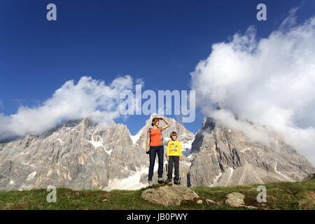 Mutter und Sohn auf einem Felsen steht und genießen die Aussicht, Baita Segantini, Dolomiten, Italien. - Stockfoto