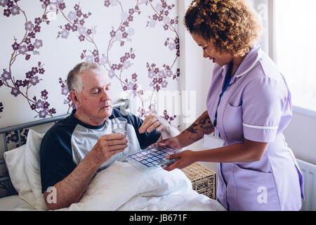 Bedbound senior Mann nach Hause Betreuer Unterstützung erhalten. Er nimmt einige Medikamente mit Wasser. - Stockfoto